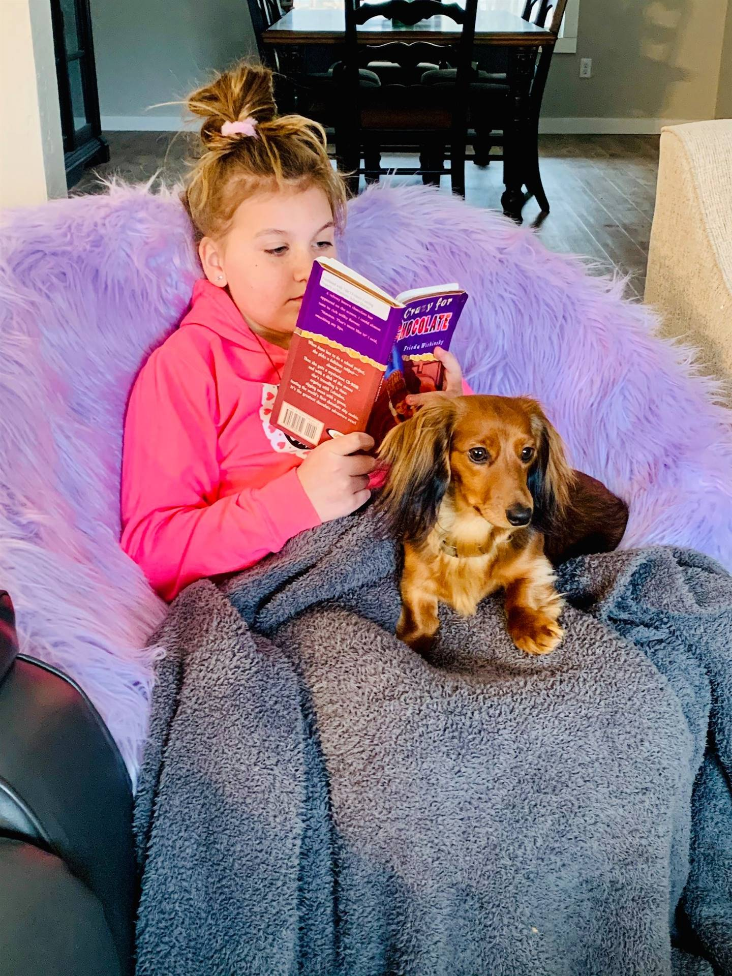 Student reading a book with a dog