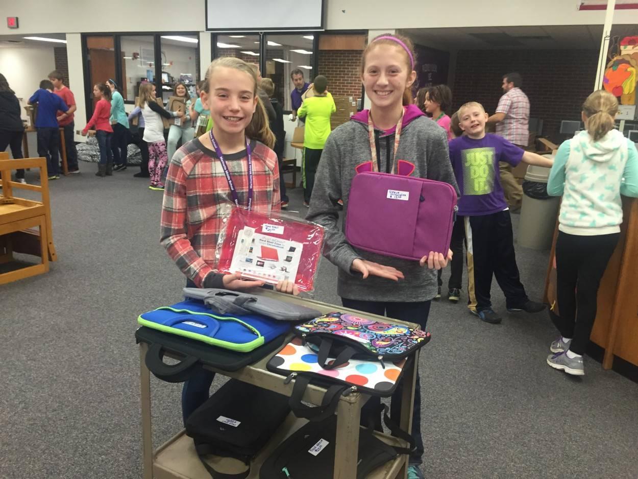 Children holding laptop bags